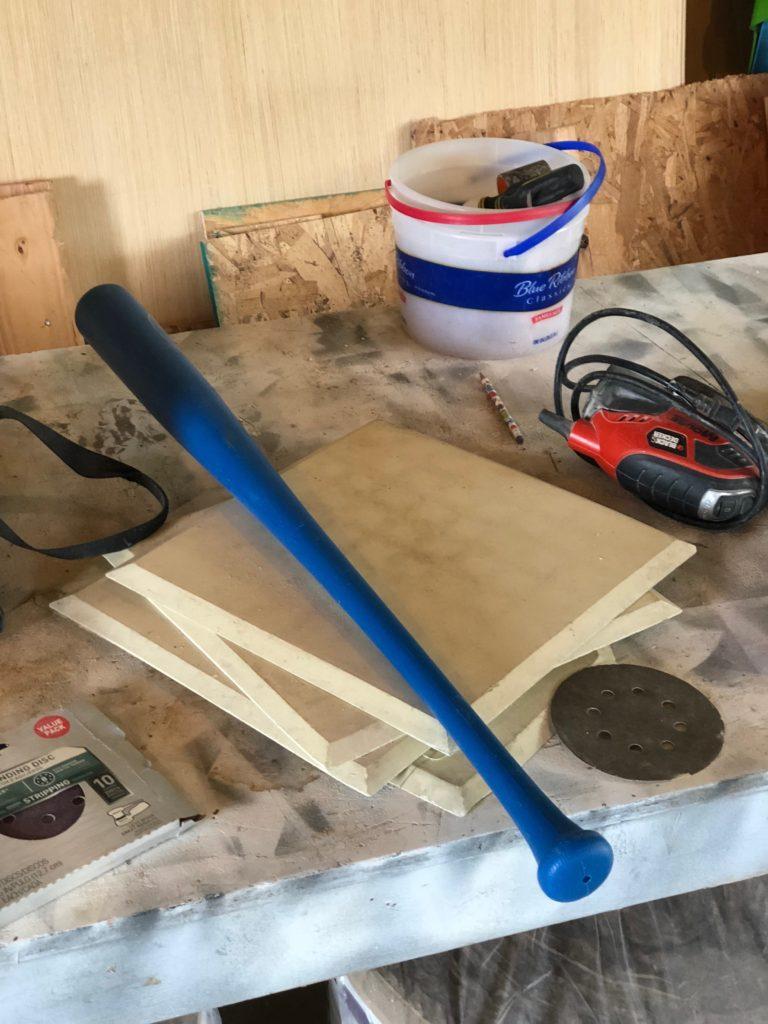 blue baseball bat with bases and sander