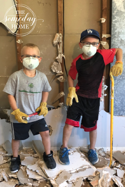 two boys with tools and dust masks, standing on top of construction rubble