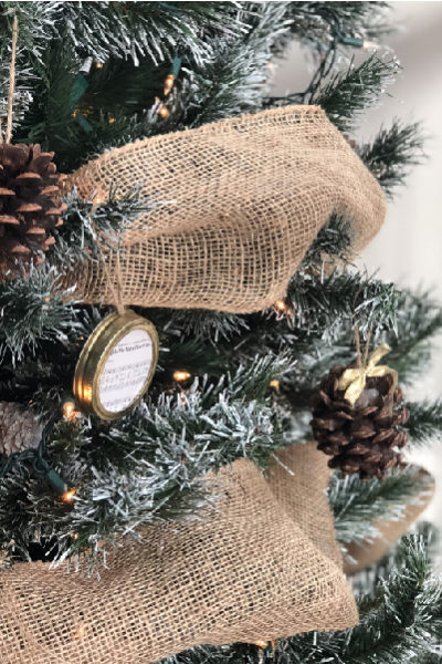 close up of christmas tree with burlap garland and pine cone ornament