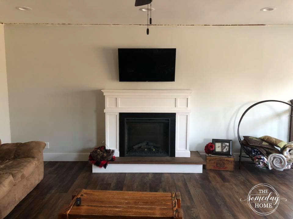 white fireplace with tv above it