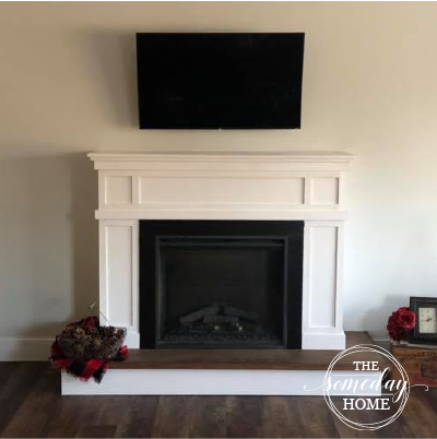 white fireplace with dark hardwood floors and tv mounted above