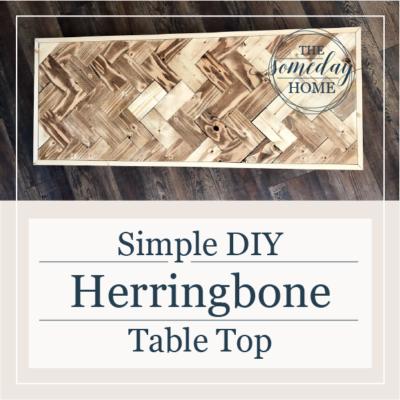 """diy herringbone table top cover photo; herringbone table top on a dark wood floor with text overlay """"simple diy herringbone table top"""