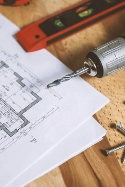 floor plans on white paper with a level, drill, screws, and tape measure